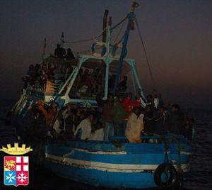 Un barcone di migranti in attesa di soccorsi al largo di Lampedusa