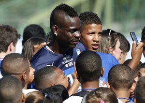 Mario Balotelli circondato dai ragazzini brasiliani in cerca di autografo (Reuters).