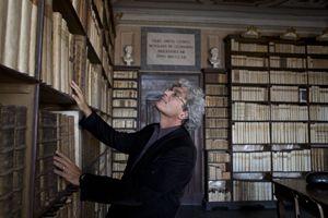 Il regista Mario Martone nella biblioteca nella casa di Leopardi a Recanati. In alto: Elio Germano.
