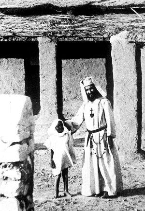 Padre Foucauld a Tamanrasset, con un bambino da lui battezzato.