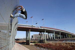 Un migrante cerca di forzare la rete che separa il Messico e gli Stati Uniti d'America. Foto Reuters.