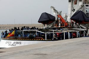 La nave Open Arms durante uno sbarco a Pozzallo e, sopra, operazioni in mare (Foto Reuters)