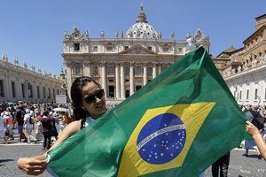 Una fedele in piazza San Pietro prima dell'Angelus con la bandiera del Brasile. Al popolo brasiliano, la cui squadra di calcio è stata eliminata dai mondiali, il Papa ha inviato un affettuoso saluto