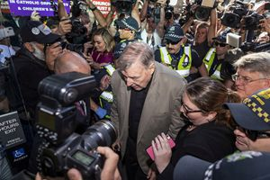 Il cardinale George Pell, 77 anni, attorniato dai giornalisti, arriva alla County Court di Melbourne (Australia) per il processo