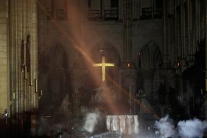 Quel che resta attorno all'altare maggiore dopo l'incendio con la Croce rimasta intatta al suo posto (Reuters)